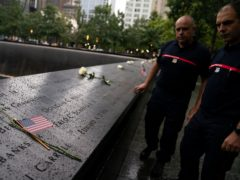 Visitors browse the south pool as flowers and American flags rest among the names of the fallen at the National September 11 Memorial & Museum (John Minchillo/AP/PA)