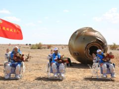 Tang Hongbo, Nie Haisheng and Liu Boming wave at the Dongfeng landing site in northern China's Inner Mongolia Autonomous Region (Xinhua/AP)