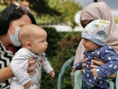 Alexandra Kenchington with her four-month old son, Barney, looking at the four-month old daughter, Madiha, of Afghan refugees (Matt Simmons/PA).