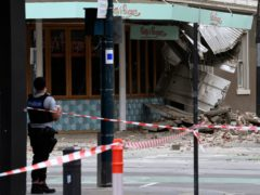 A police officer closes an intersection where debris is scattered in the road after an earthquake damaged a building in Melbourne (James Ross/AAP Image via AP)