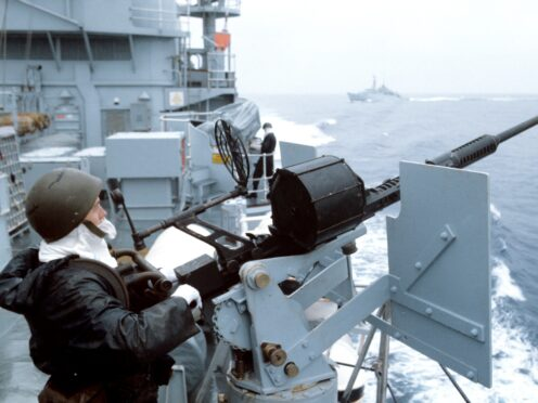 A Royal Navy sailor manning an anti-aircraft gun aboard HMS Hermes as the British Taskforce sails south to the Falkland Islands (PA)