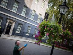 A man waters hanging baskets in Downing Street, London (Aaron Chown/PA)