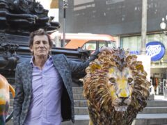 Rolling Stones guitarist Ronnie Wood with the lion he designed (Joshua Bratt/PA)