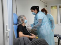 Medical staff administer the third dose booster Pfizer vaccine shot to a woman at the Matei Bals hospital in Bucharest, Romania (Vadim Ghirda/AP)