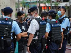 A pro-democracy protester is surrounded by police officers (Vincent Yu/AP)
