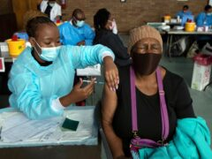 A woman receives a vaccine from a healthcare worker in South Africa (Themba Hadebe/AP)