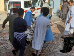 People carry a bombing victim in Kunduz province, northern Afghanistan, Friday, Oct. 8, 2021. A powerful explosion in a mosque frequented by a Muslim religious minority in northern Afghanistan on Friday has left several casualties, witnesses and the Taliban's spokesman said. (AP Photo/Abdullah Sahil)