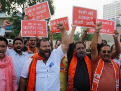 Supporters of Hindu right-wing Vishwa Hindu Parishad (VHP) or World Hindu Council and Bajrang Dal hold placards as they shout slogans during a protest in Ahmedabad against the recent targeted killings of civilians in Indian-controlled Kashmir (Ajit Solanki/AP)
