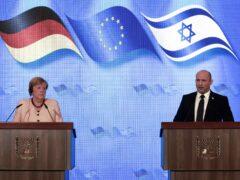 German Chancellor Angela Merkel and Israeli Prime Minister Naftali Bennett give a joint press conference following their meeting in Jerusalem (Menahem Kahana/Pool via AP)