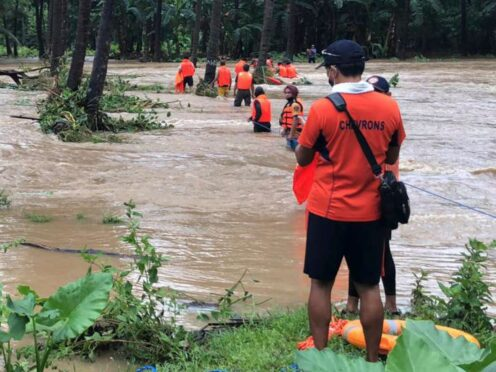 In this photo released by the Philippine Coast Guard, rescuers help residents navigate floodwaters caused by Tropical Storm Kompasu at the municipality of Brooke's Point, Palawan province in southwestern Philippines on Tuesday, Oct. 12, 2021. A number of people have been killed and others were reported missing in landslides and flash flood set off by a storm that barreled through the tip of the northern Philippines overnight then blew away Tuesday, officials said. (Philippine Coast Guard via AP)