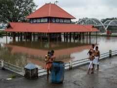 Hindu devotees walk back after performing rituals, past an inundated Shiva temple on the banks of the Periyar River following heavy rains in Kochi, Kerala state, India, Tuesday, Oct. 12, 2021. (AP Photo/R S Iyer)