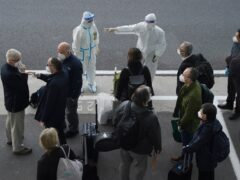 Workers in protective clothes direct members of the WHO team on their arrival in Wuhan (AP)