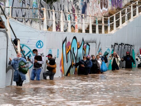 People wade through water after evacuating a bus stuck in a flooded underpass in Athens (Thanassis Stavrakis/AP)