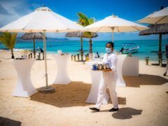 A waitress wears a medical face mask, in accordance with Government guidelines, while clearing beach tables at the Preskill resort in Mauritius (Ben Birchall/PA)