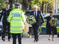 Chief Constable Ben-Julian Harrington, Labour leader Sir Keir Starmer, Prime Minister Boris Johnson and Home Secretary Priti Patel carry flowers as they arrive at the scene near Belfairs Methodist Church in Leigh-on-Sea, Essex, where Conservative MP Sir David Amess died after he was stabbed several times at a constituency surgery on Friday. (Dominic Lipinski/PA)