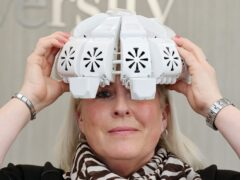 Tracy Sloan with the infrared light therapy helmet that she tried to help improve her memory (Durham University/PA)