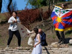 """A police officer tries to stop protesters displaying a Tibetan flag and a banner reading """"No genocide games"""" during the lighting of the Olympic flame at Ancient Olympia site, birthplace of the ancient Olympics in southwestern Greece (Thanassis Stavrakis/AP)"""