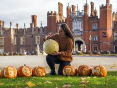 Palace gardener Justine Howlett adds the finishing touches to a pumpkin (Steve Parsons/PA)