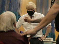 Prime Minister Boris Johnson watches a Pfizer booster vaccination (Matt Dunham/PA)