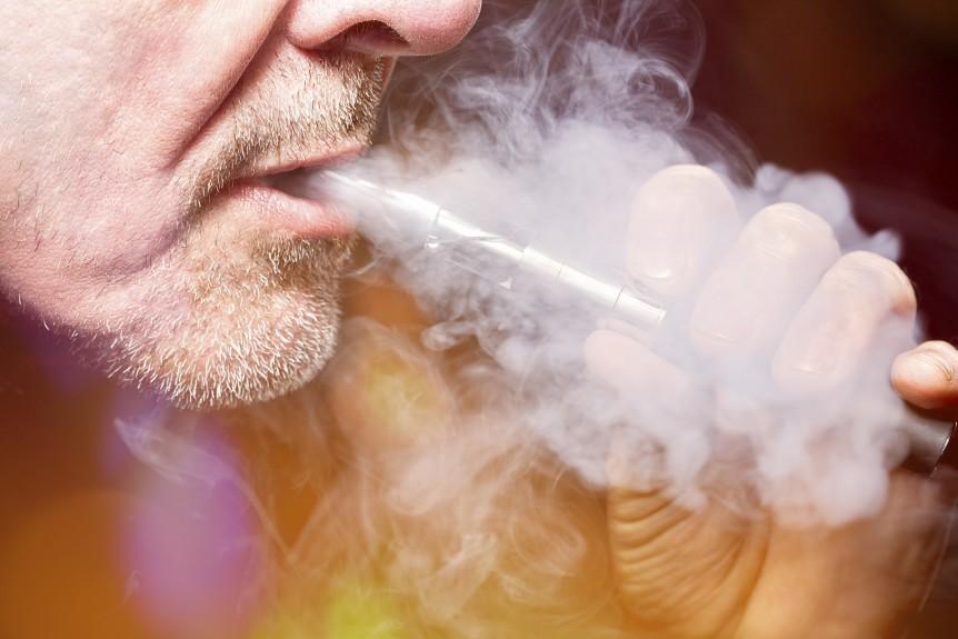 close up portrait of a man smoking an e-cigarette