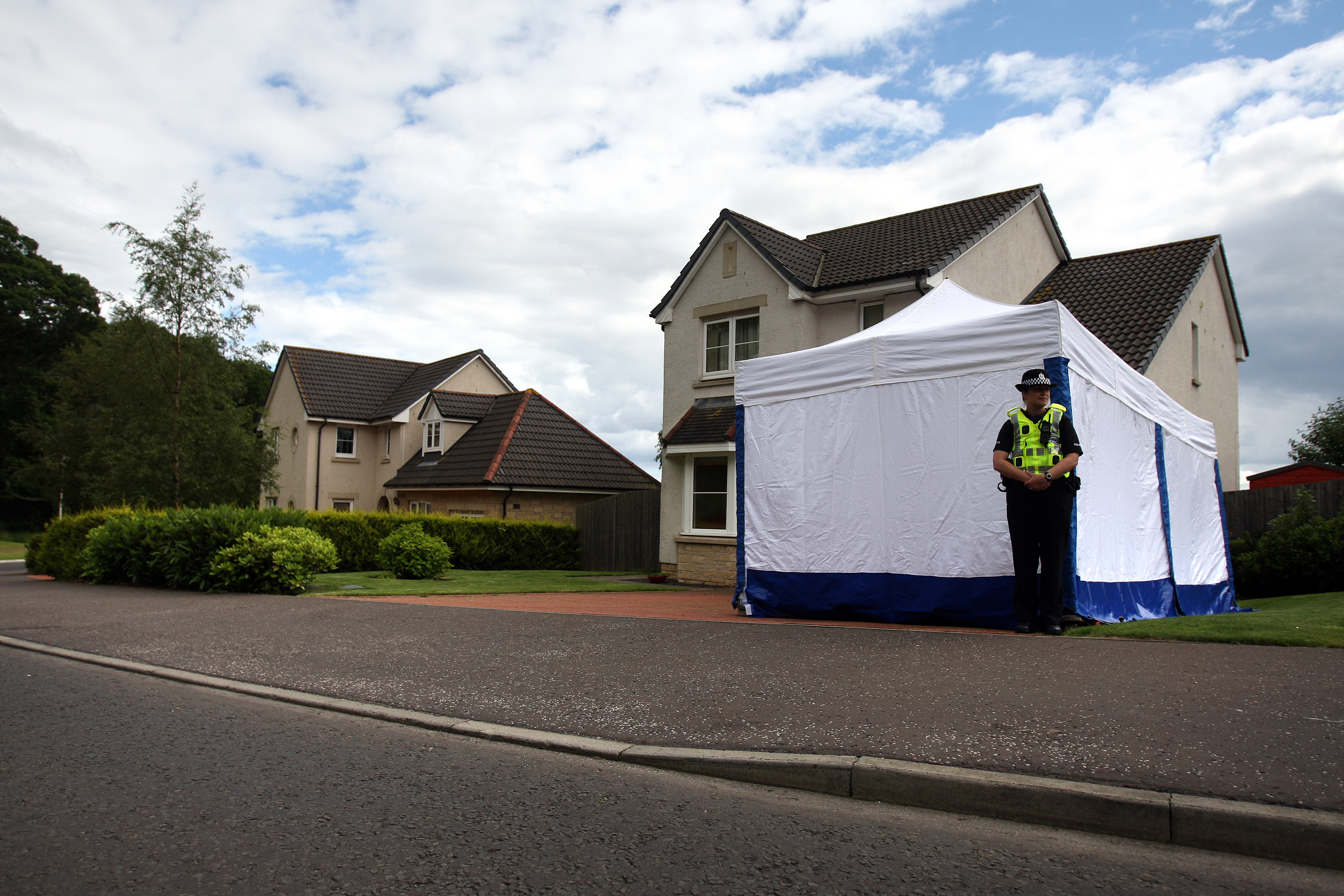A police officer stands outside the property in Ballumbie following the incident