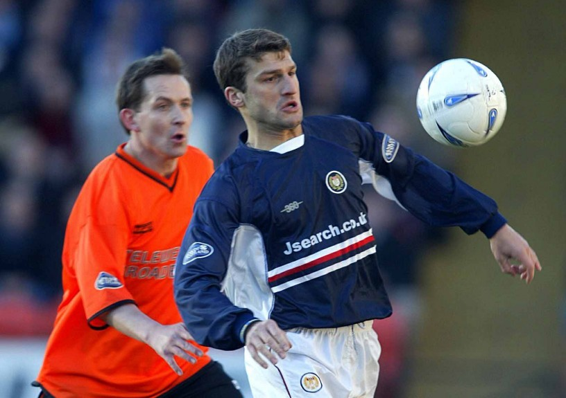 Georgi Nemsadze knocks the ball past Billy Dodds during a derby game in 2003.