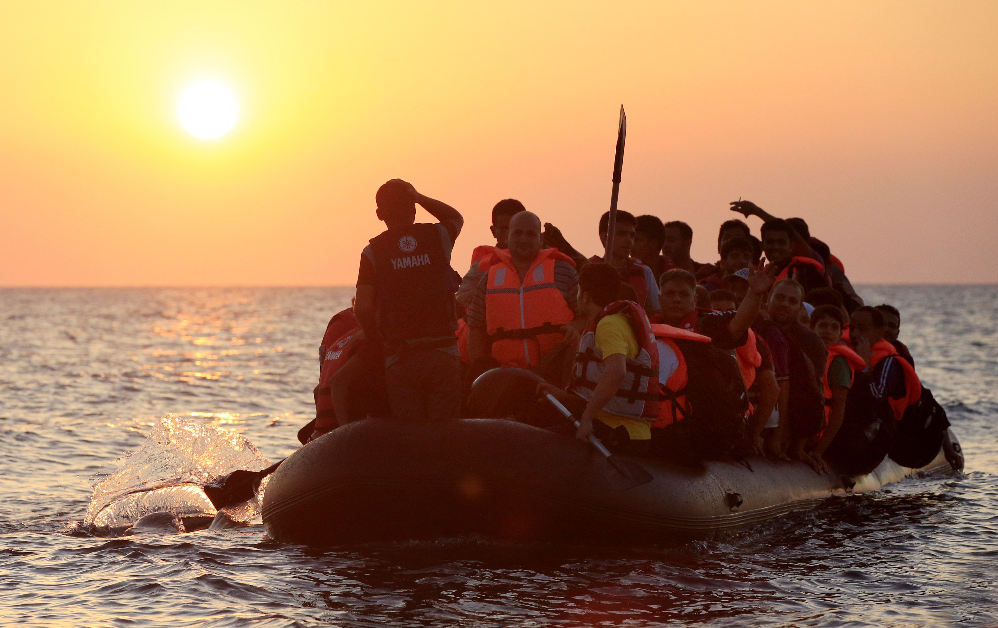 Migrants and refugees paddling a rubber dinghy close to the beach at Psalidi near Kos Town, Greece.