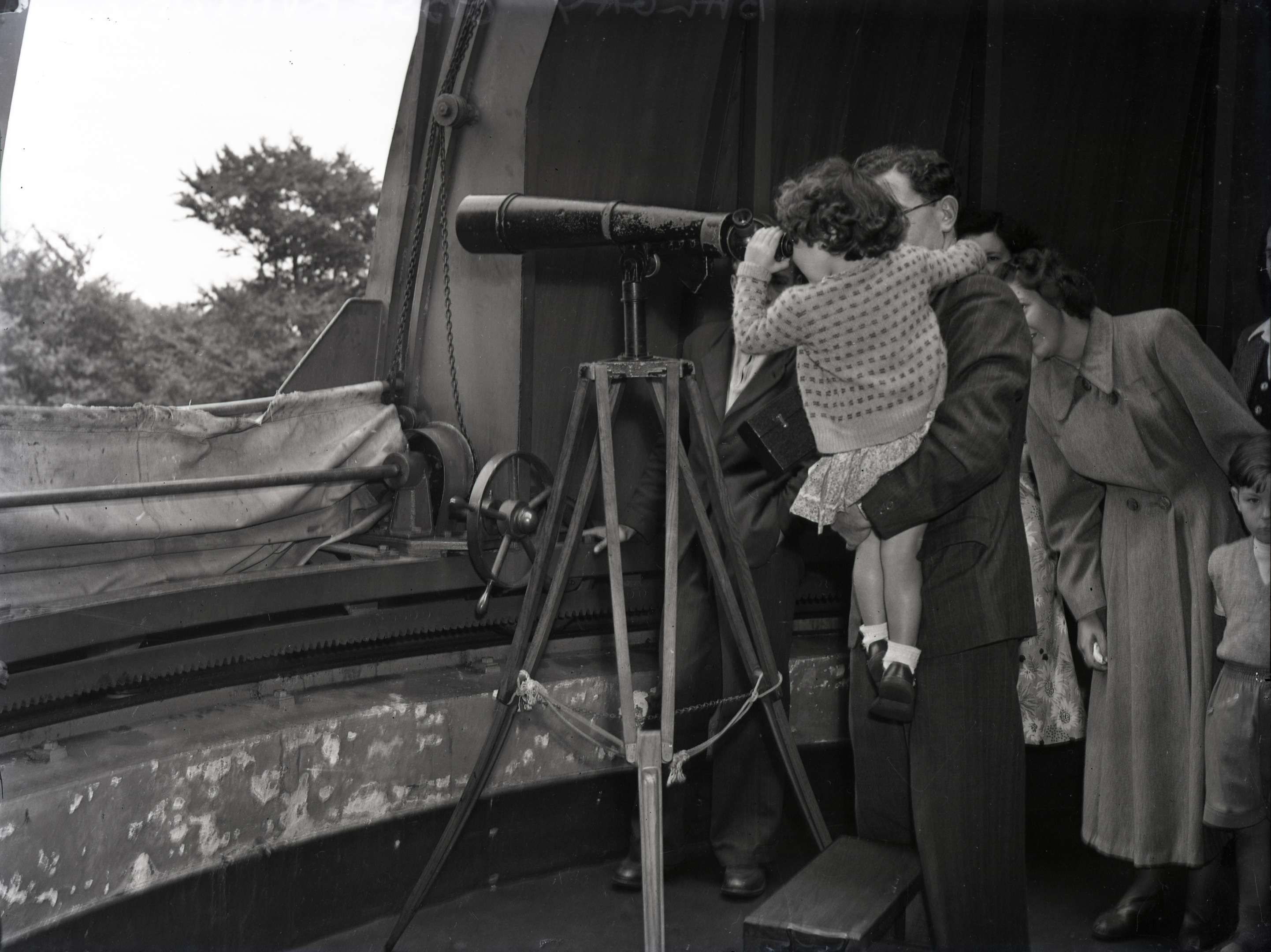 A family peers through one of the smaller telescopes at the observatory in 1934.