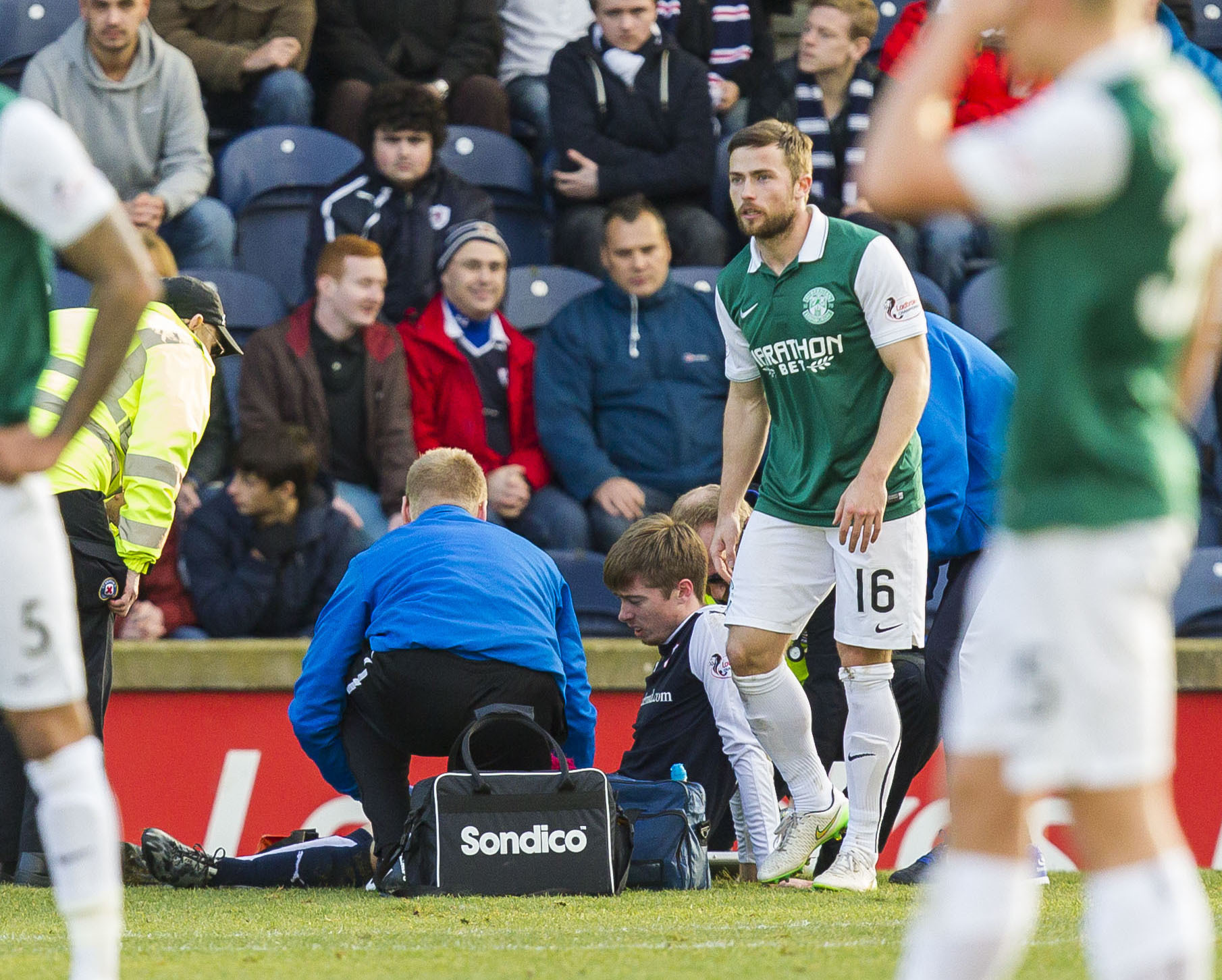 Craig Wighton receives treatment after a challenge from Hibs Lewis Stevenson