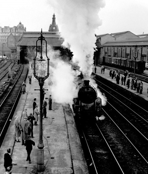 A steam engine leaves the city.
