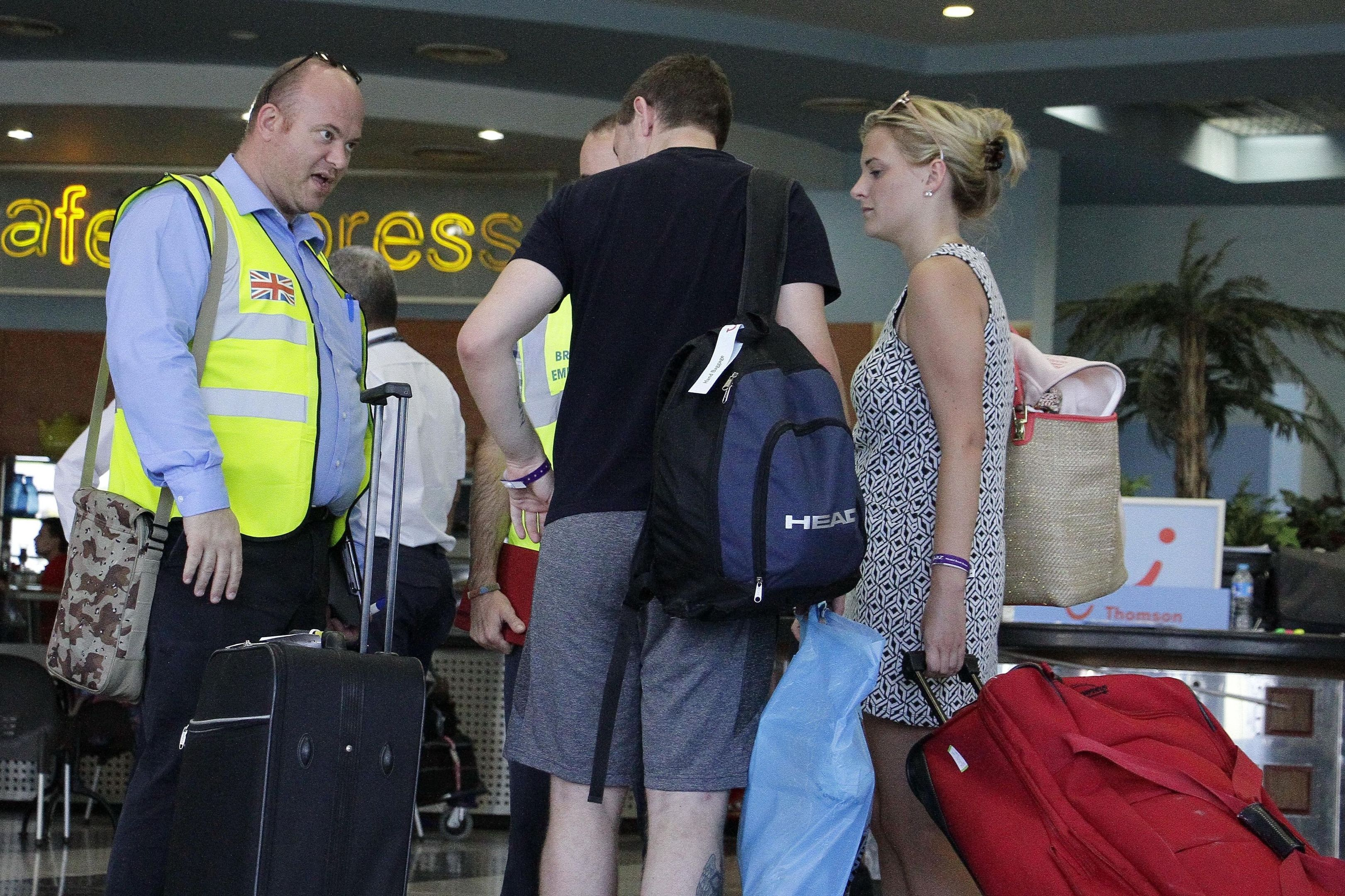 Representatives of the British government assist passengers preparing to depart from Sharm el-Sheikh Airport