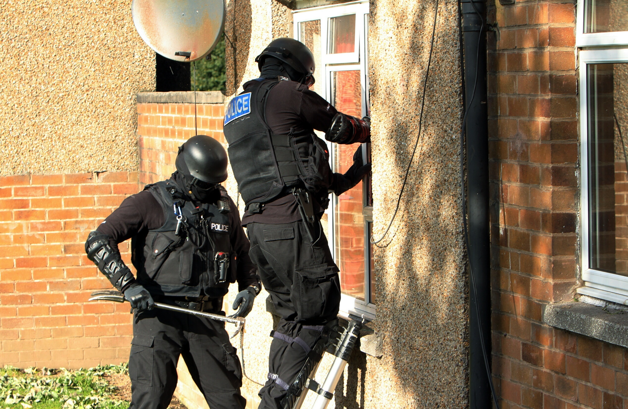 Police carry out a drugs raid on a house.