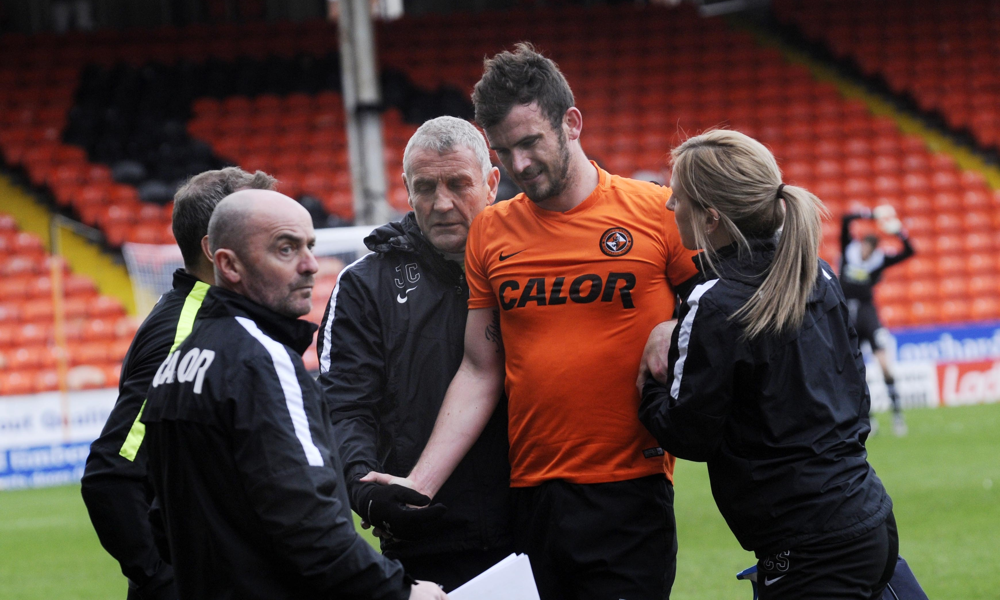 Gavin Gunning explains to Dundee United's medical team his injury. Picture by David Martin.