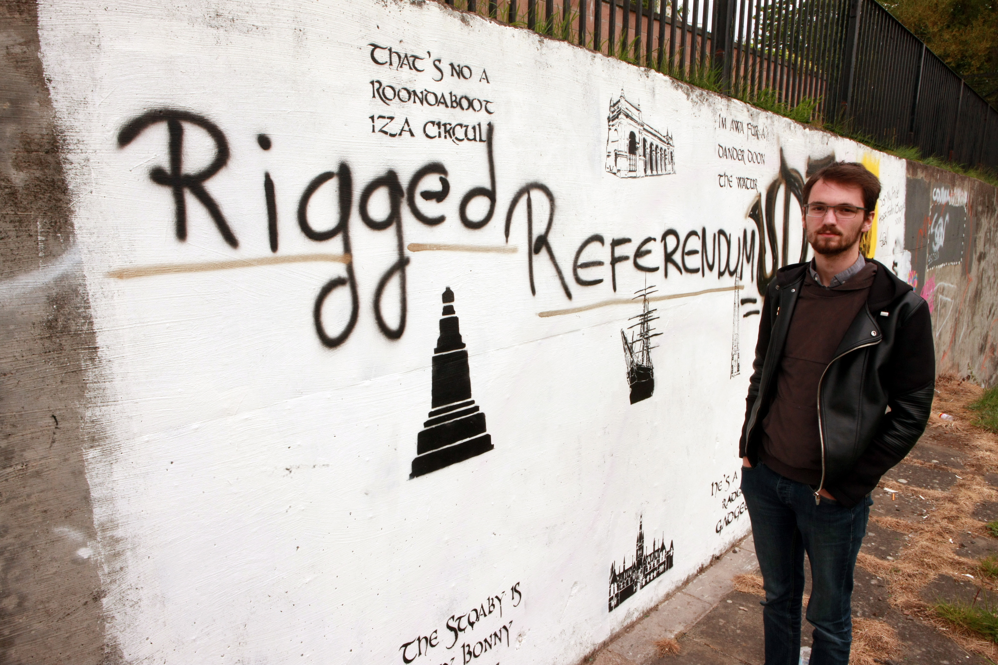 Connor Beaton next to the vandalised mural, which has been hit with graffiti.