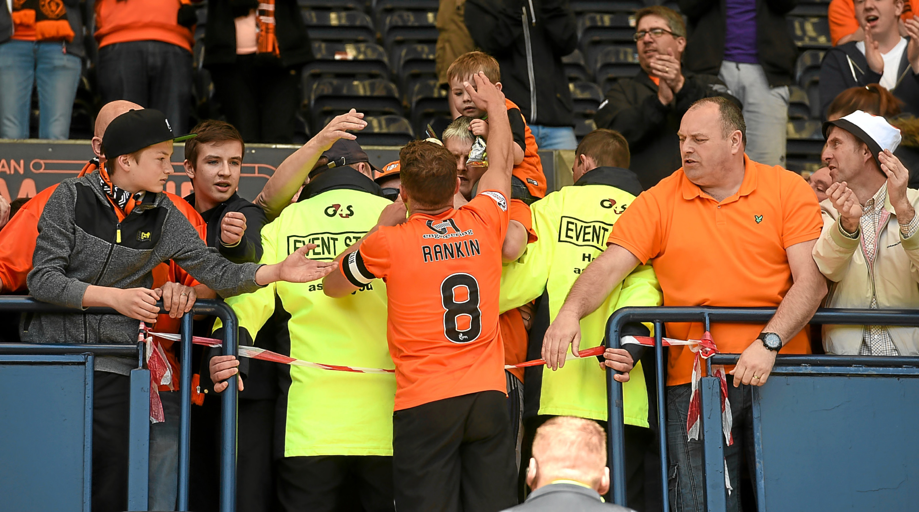 Stand-in skipper John Rankin hands his boots to a young fan as he says his farewells to the travelling Tangerines support in his final game for Dundee United at Kilmarnock on Saturday.