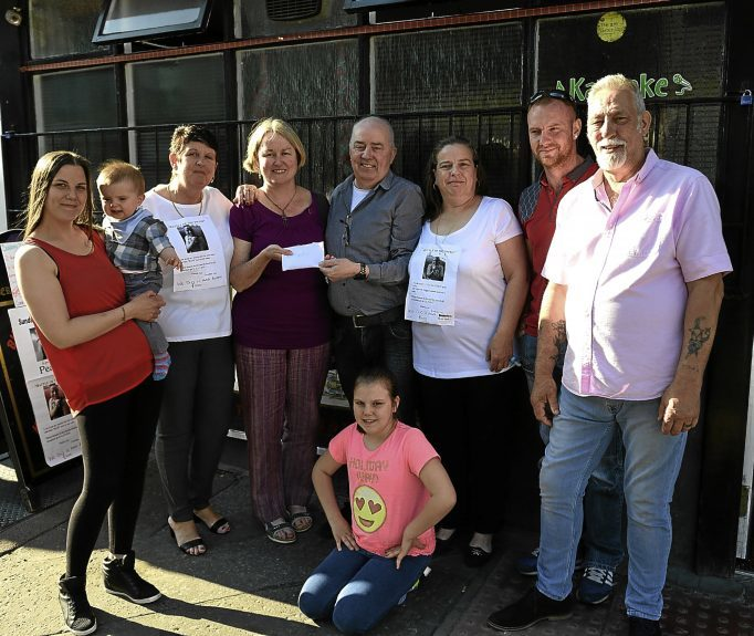 Vicki, holding Jackson, and Evelyn are pictured with some of the people who attended the fundraiser