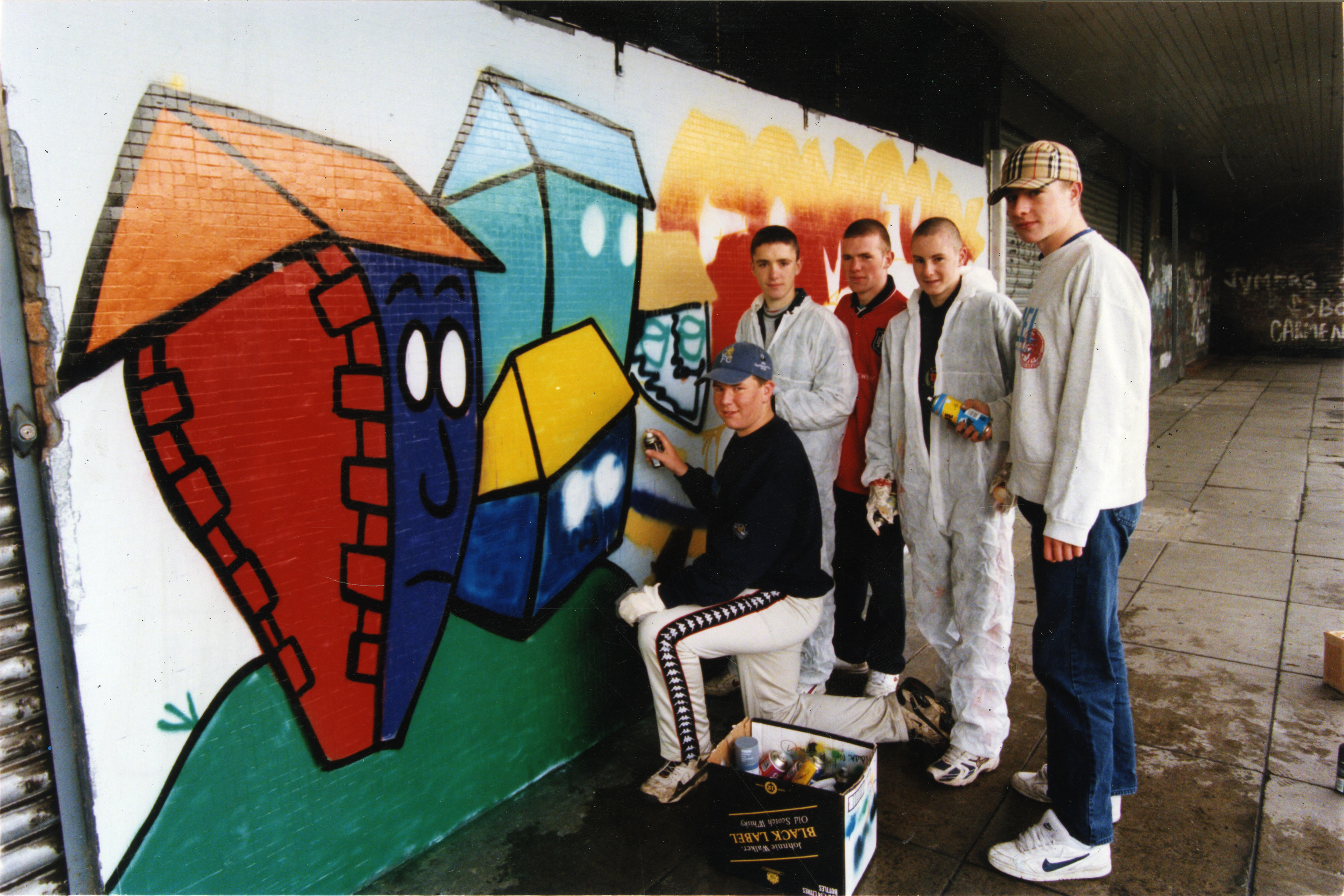 Graffiti artists paint the Happyhillock shops to deter youngsters from spraying walls. (October 1998)