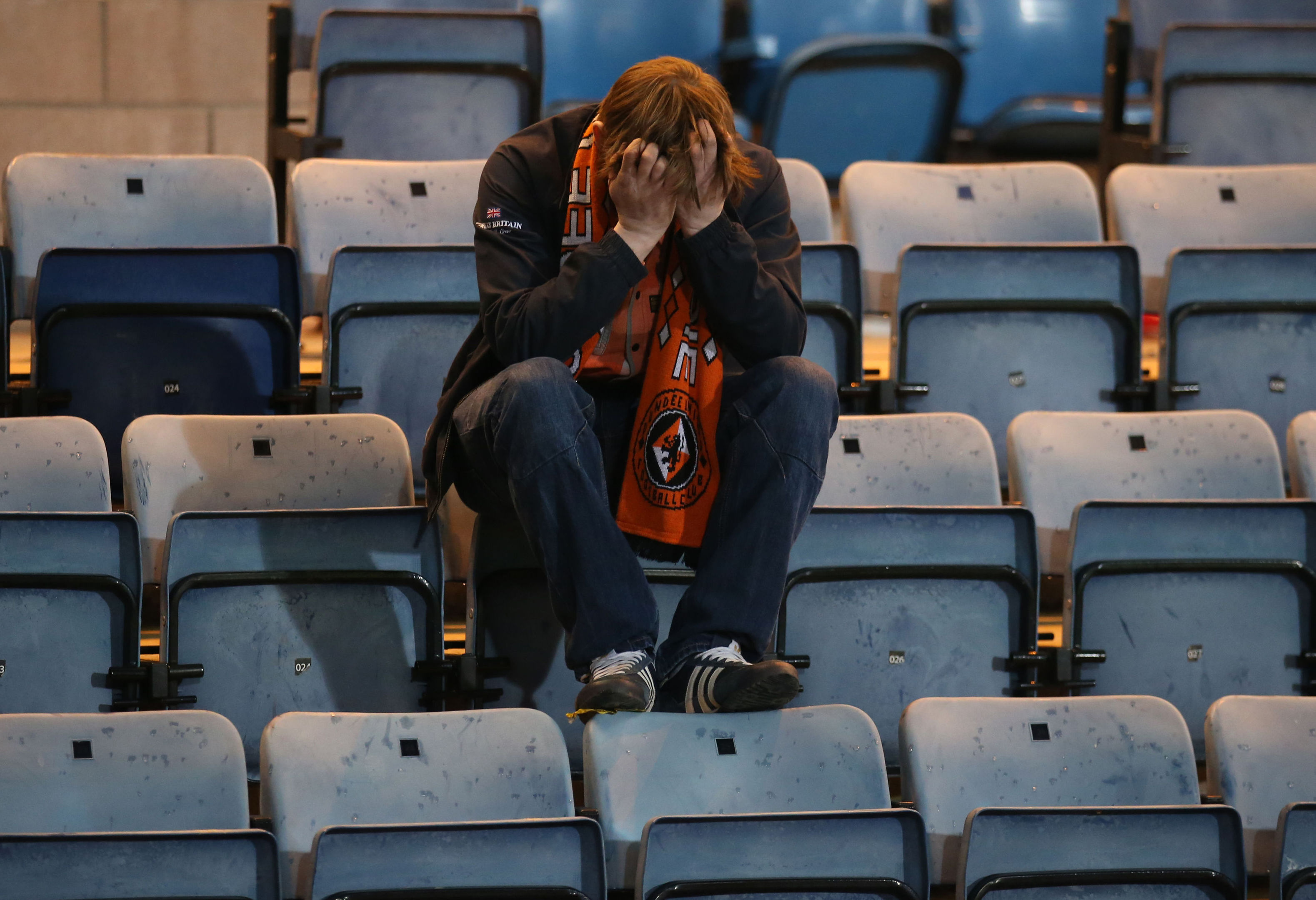 A Dundee United fan appears dejected after his side is relegated at Dens Park