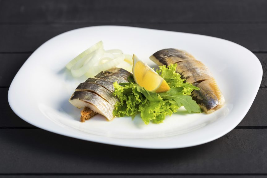 Dish of slices herring fish with greens, lemon and onion