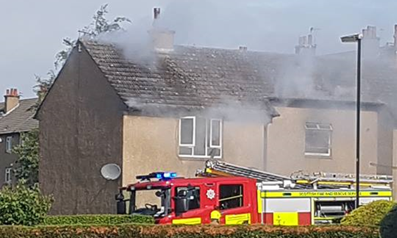 A fire engine at the scene with smoke coming from the property.