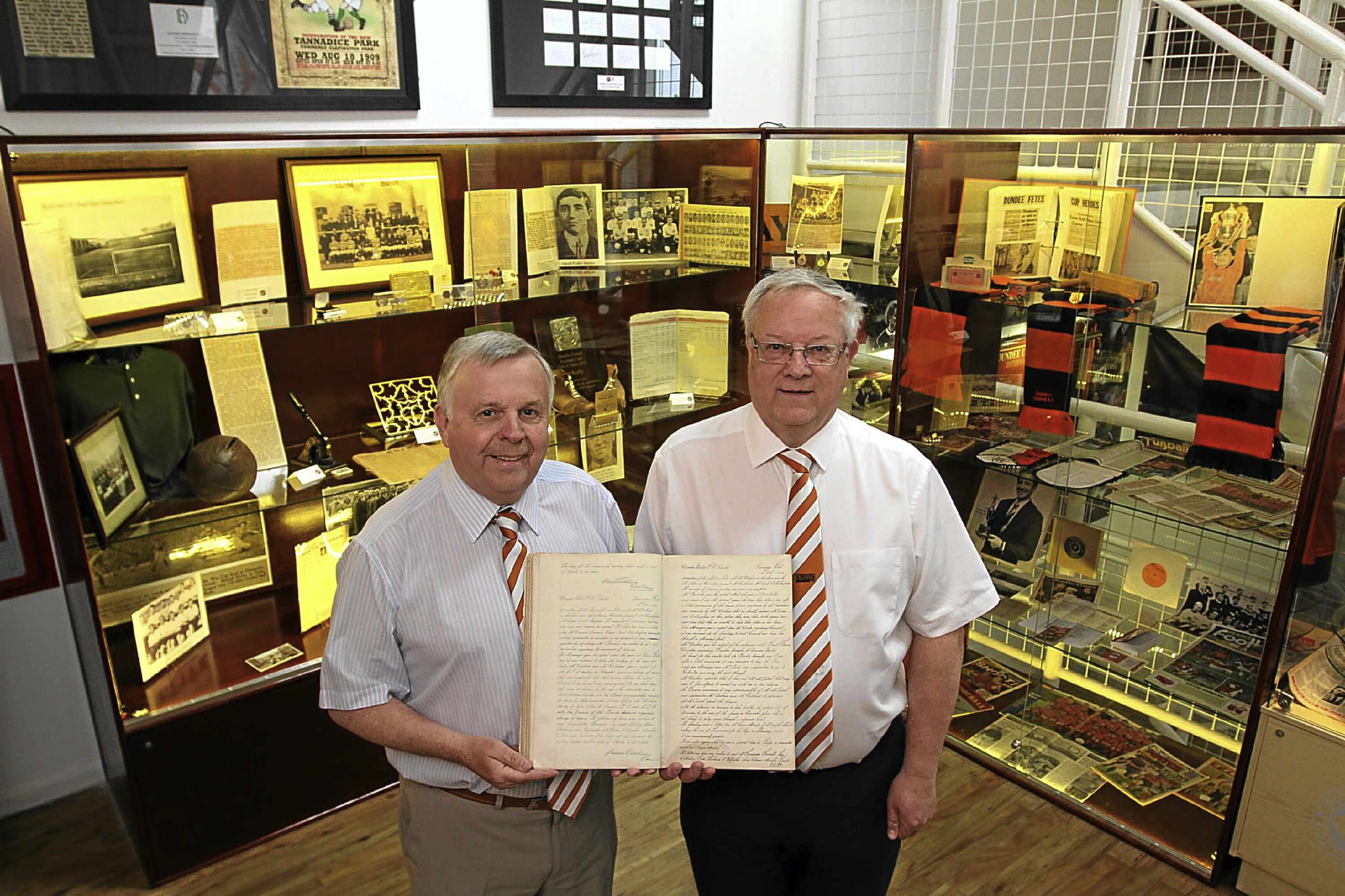 Tom Cairns (left) and Peter McBride, who have put together the new Dundee United museum at Tannadice, hold a minute book of board meetings from the 1920s.