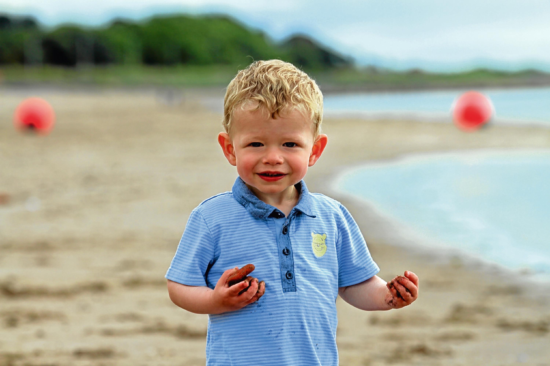 Adam Urquhart, aged one, from Kirriemuir, plays on the beach