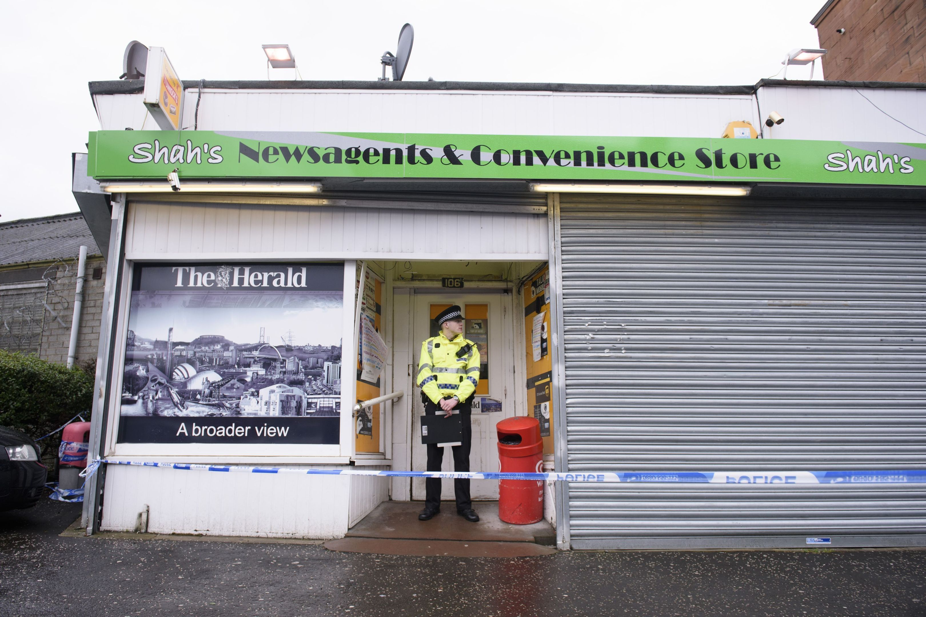 A police officer stands guard outside Asad Shah's shop in the Shawlands area of Glasgow.