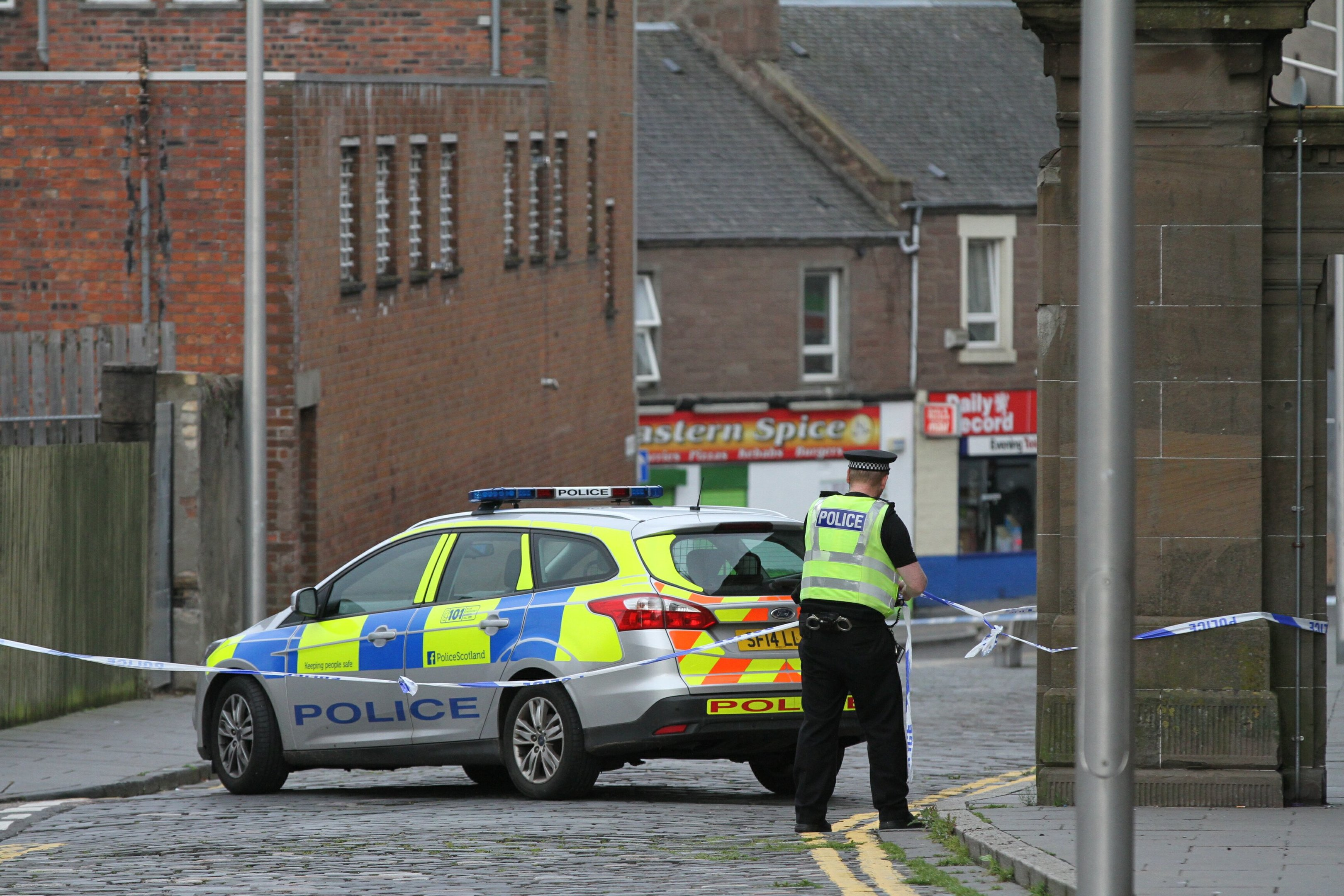 A police officer at the scene in Lochee.