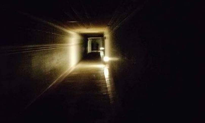 This eery image appears to show two figures at the end of the long empty corridor.