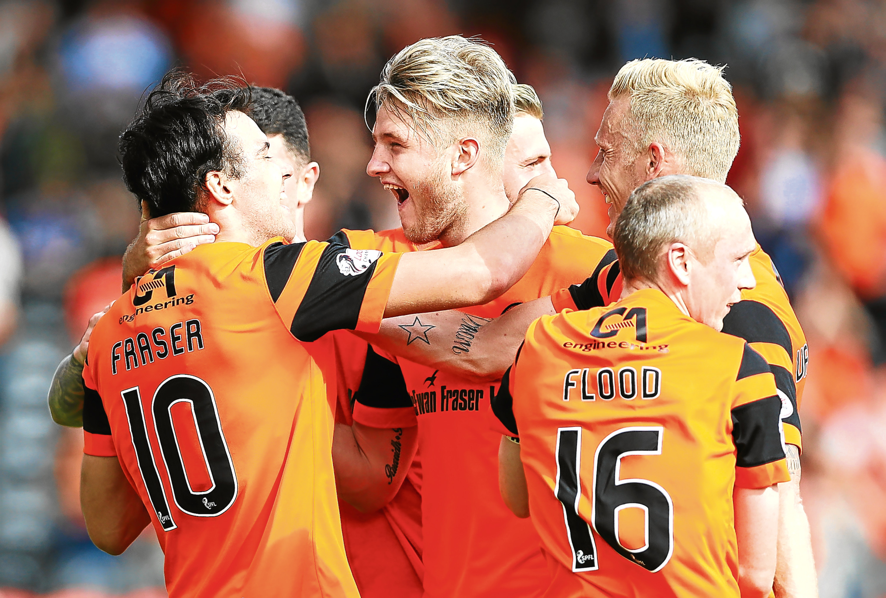 Scott Fraser is congratulated by his team-mates after he scores Dundee United's second goal at Tannadice yesterday.