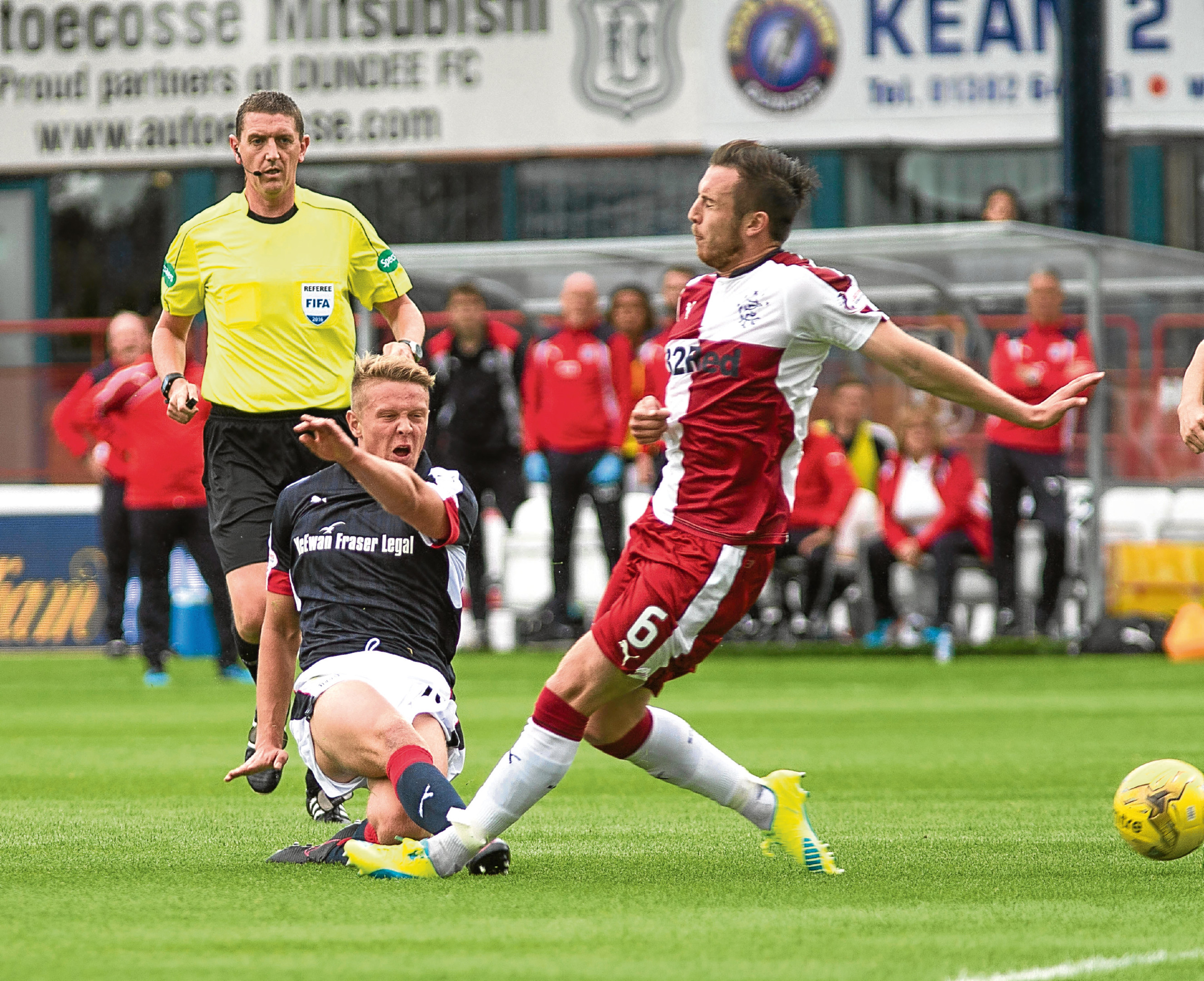 Dundee midfielder Mark O'Hara gets a shot away despite the attentions of Rangers defender Danny Wilson at Dens on Saturday. Picture by David Young