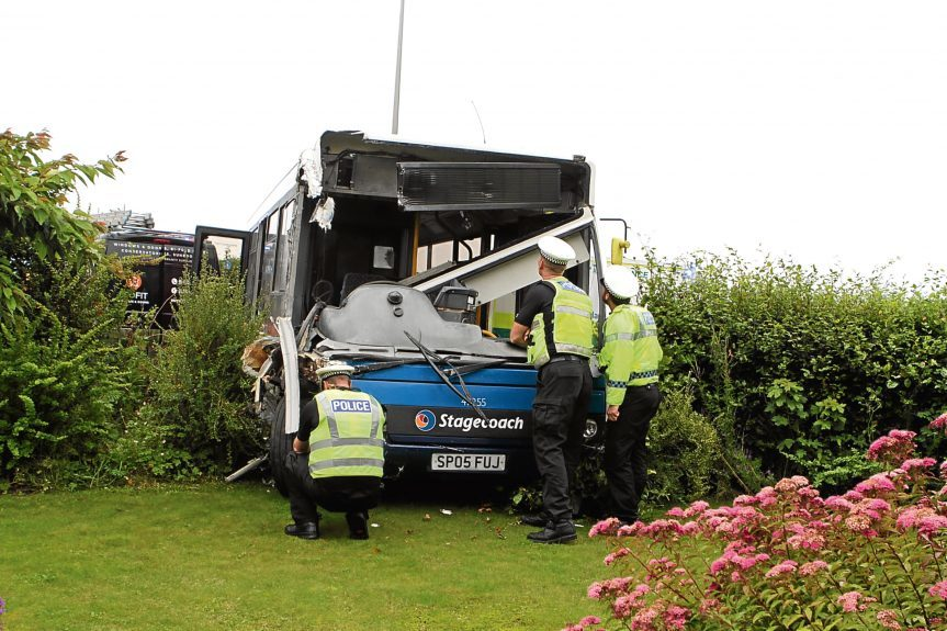 Police inspect the bus that came to rest in a garden.