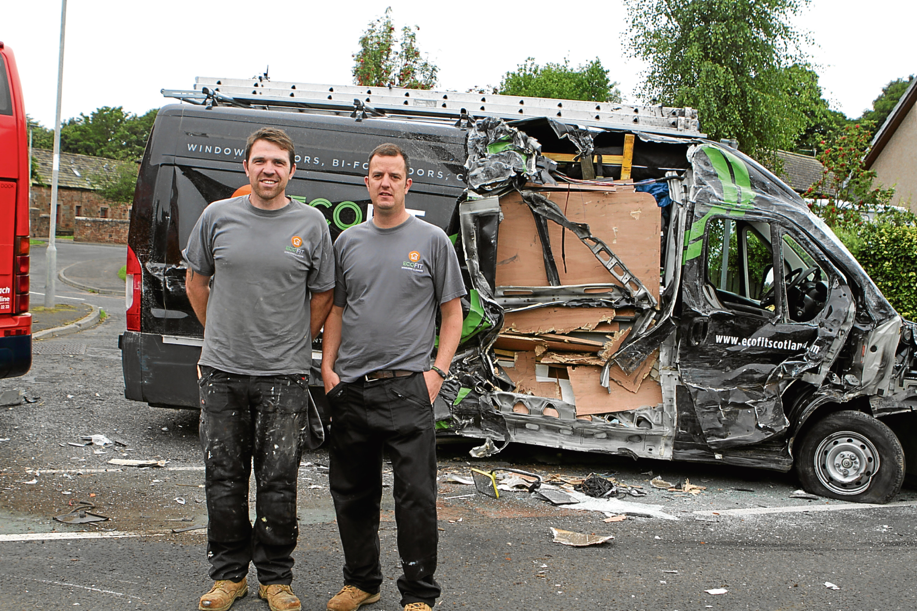 Garry Myles and Paul Reid stand in front of the damaged van.