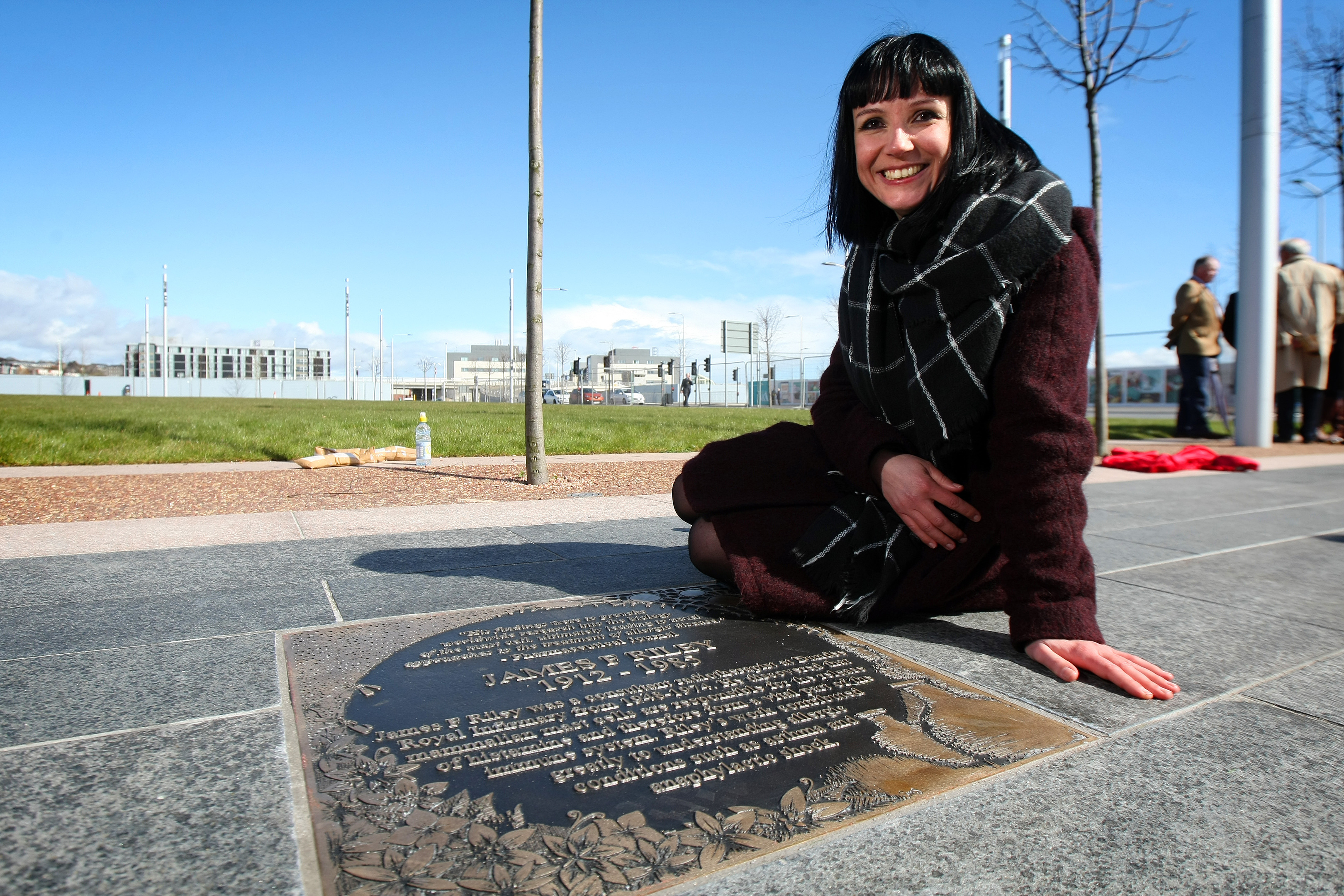 Artist Suzanne Scott next to one of the plaques.